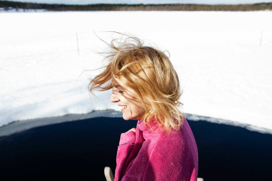 A smiling woman dressed in a pink bathrobe with a hole for ice swimming in the background.