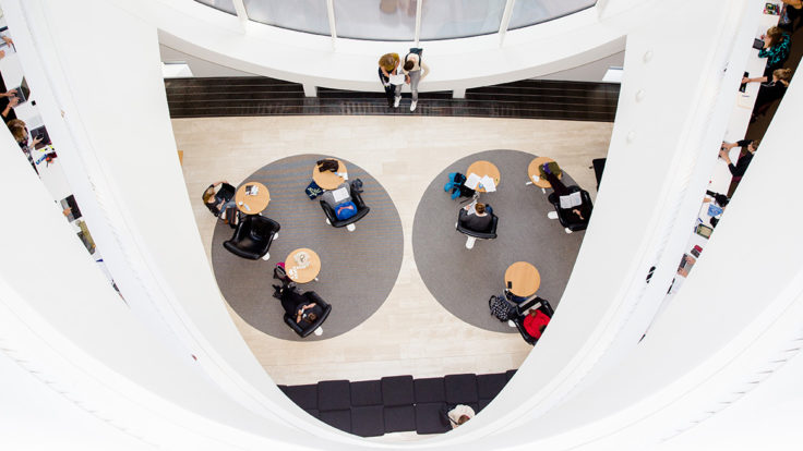 The library of University of Helsinki, photo taken from an upper floor towards the lower floors shows people studying.