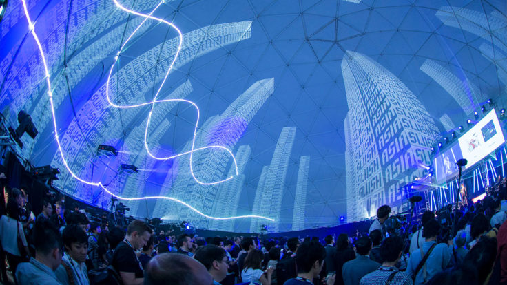 A photo from Slush Japan event shows a large crowd of people gathered in a dome-looking building.