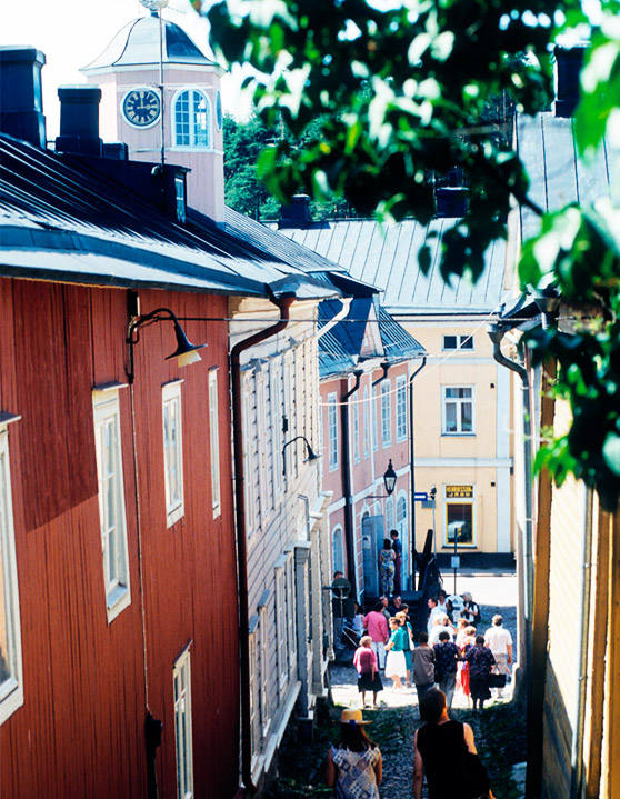 People walking on a cobblestone street between colourful wooden buildings.