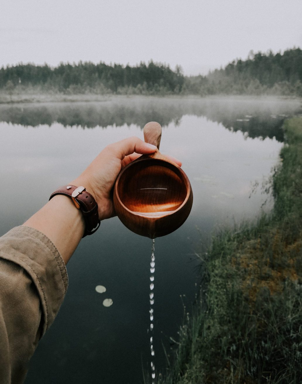 Woman pouring water from a kuksa wooden cup in front of a misty lake in the forest