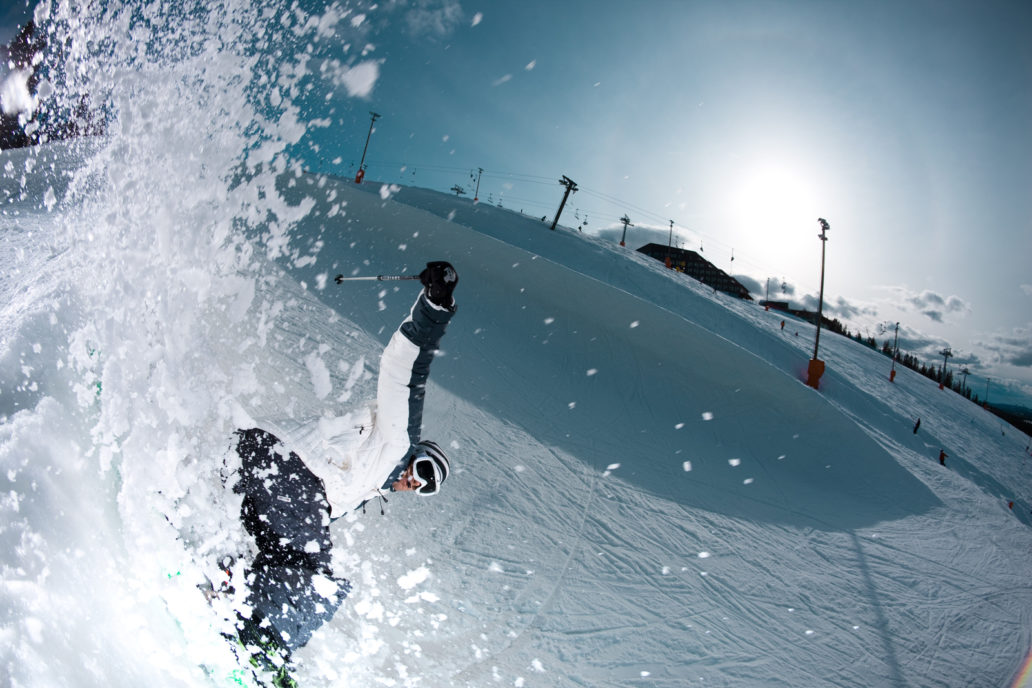 A man doing tricks on skis, the snow is whirling.