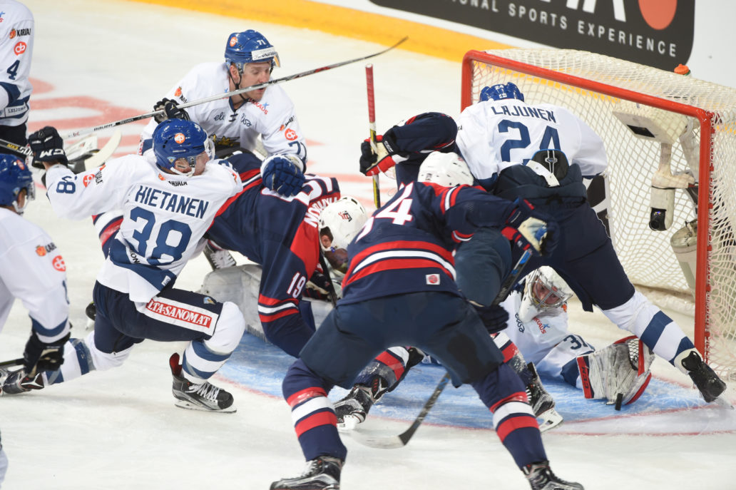Ice hockey players scuffling at the goal.