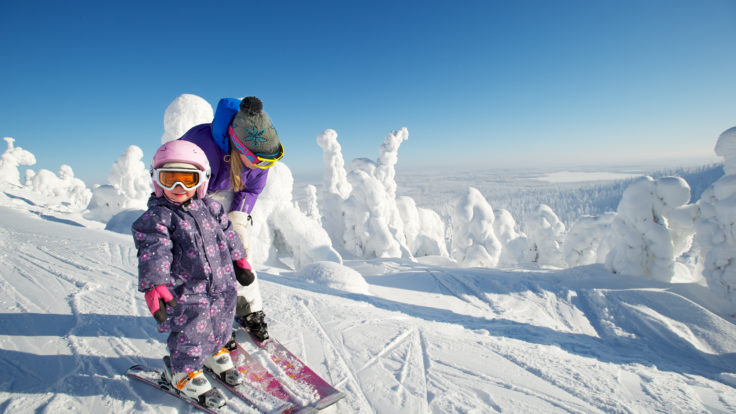 Two children on downhill skis in a snowy landscape.