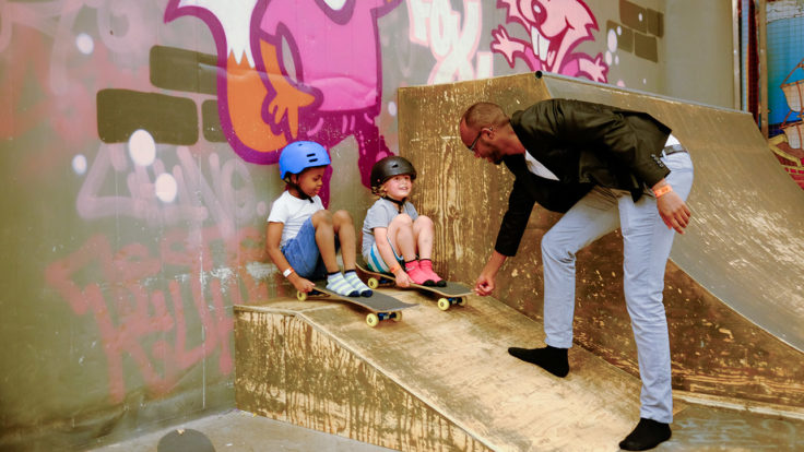 A man guiding two small children who are sitting on skateboards on a skateboard ramp.