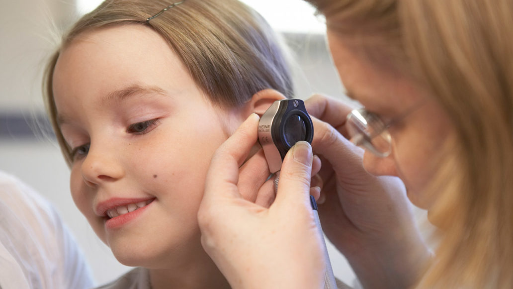 A doctor looking into a child's ear with an instrument.