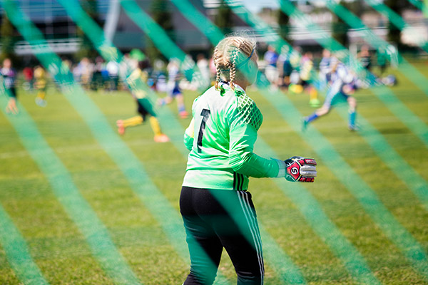 A female football goalkeeper pictured from behind.