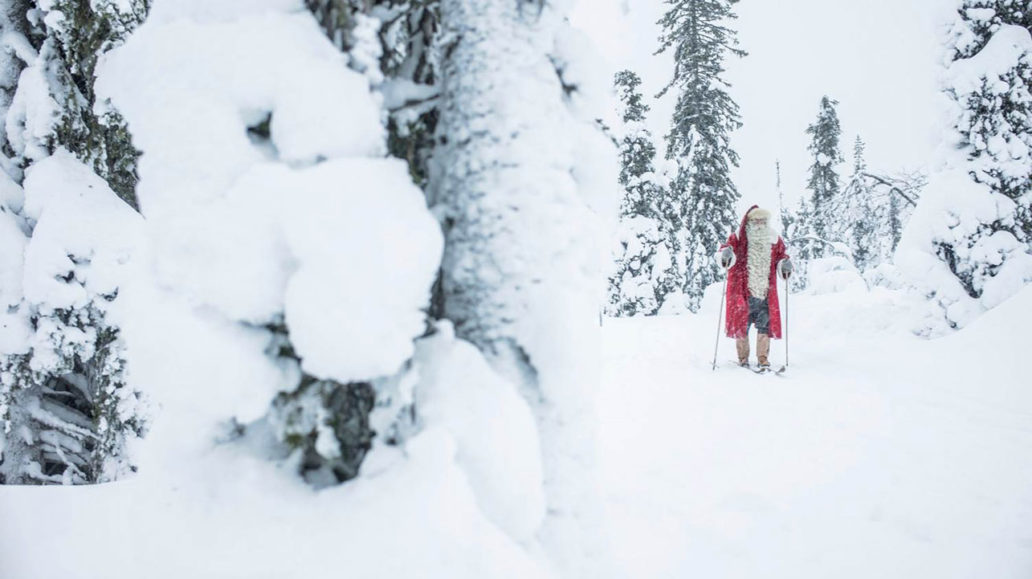 Santa Claus skiing in a snowy forest.