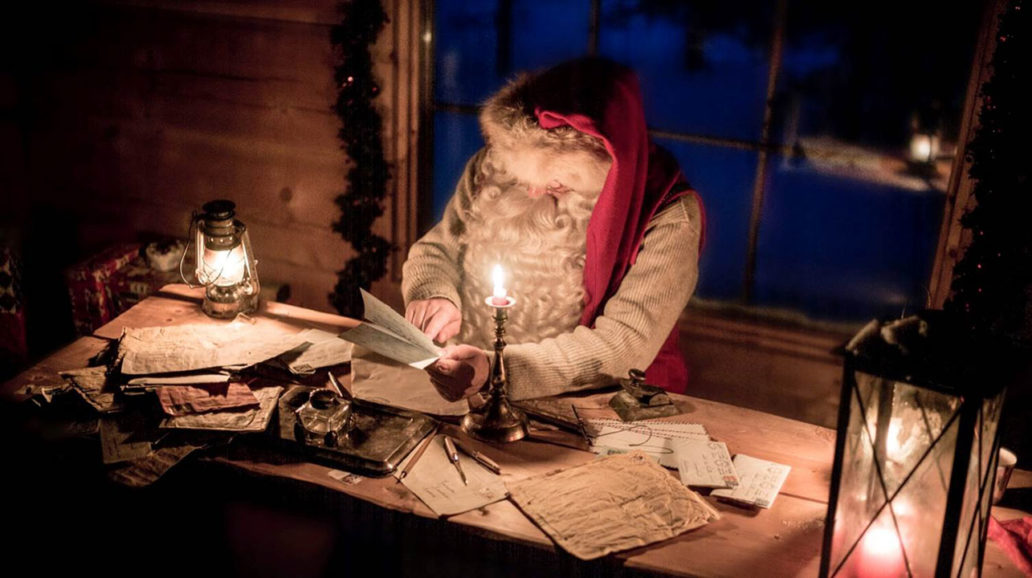 Santa Claus sitting in candlelight at his desk, reading letters.