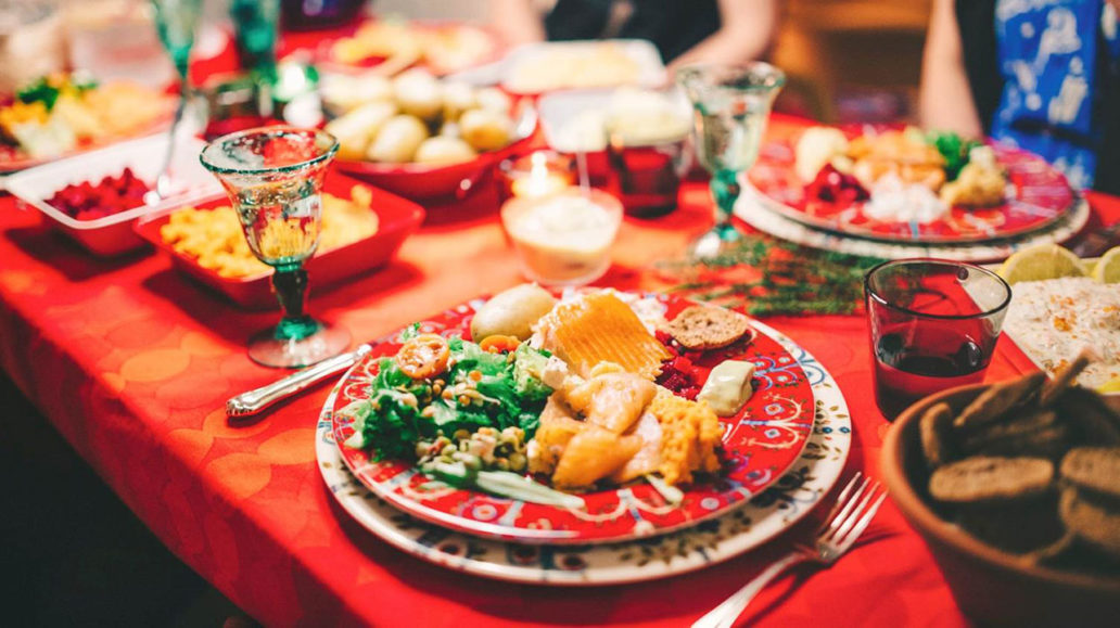 A table set up for Christmas; a red tablecloth and plates filled with food.