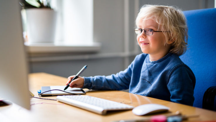 A smiling child with glasses looking at a computer screen while writing something on a digital writing pad.