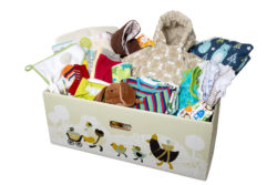 A photo of the Finnish baby box. A cardboard box full of clothes, toys and other utensils for a baby.