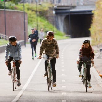 Three smiling people cycling on a wide street, people jogging behind them.