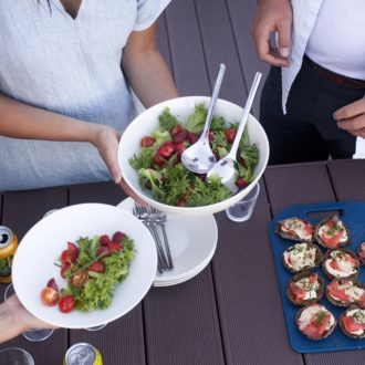 A person offering a bowl of salad for two people waiting, more food on the table.