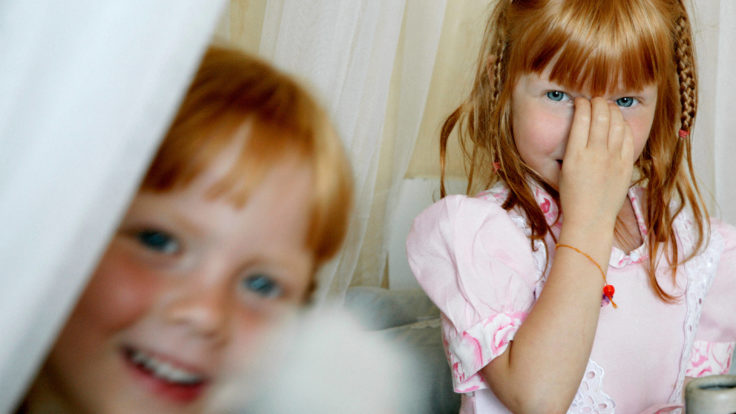 Two smiling kids; the other one closer and a little blurred, the other in the back, partly covering her face with her hand.