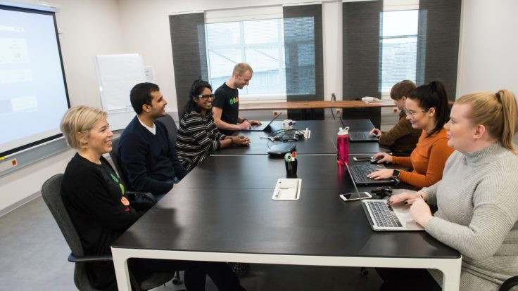 Seven smiling people sitting in a meeting at a big table, some working on laptops.