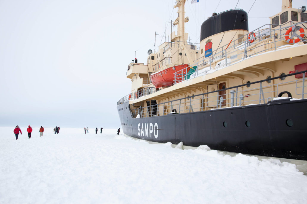 People walking on sea ice next to icebreaker ship Sampo.