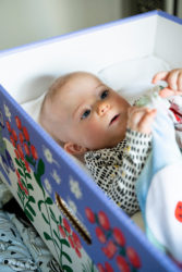 Baby in a Kela's baby box looking at a toy
