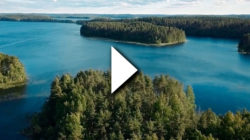 A landscape featuring a lake and some land with forest on. A video play symbol on top.