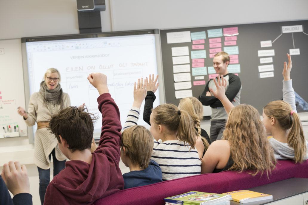 Children raising their hands at school.