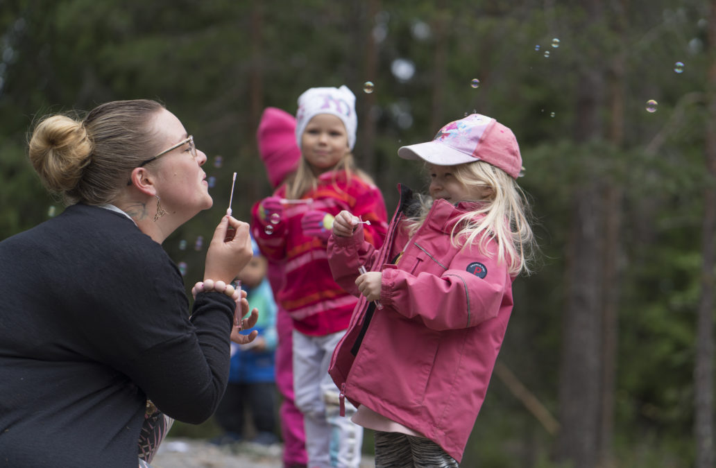 Woman blowing soap bubbles with kindergarden children.