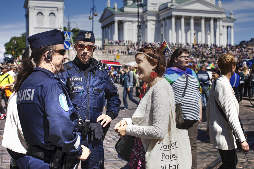 Woman talking to two police officers in a event in a square.