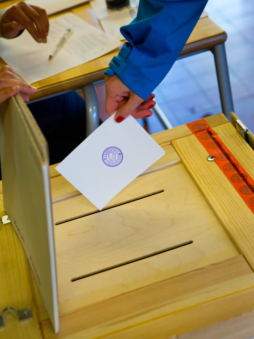A hand putting a ballot in a box.