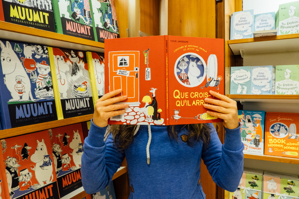 A person holding a Moomin book in a bookshop.