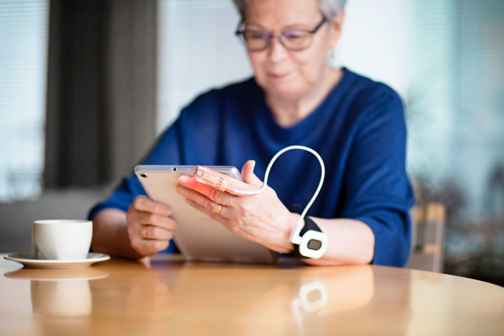 An elderly woman holding a tablet with a health device around her wrist.