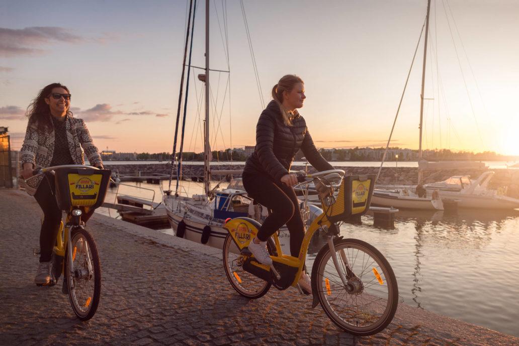 Women cycling at a harbor.