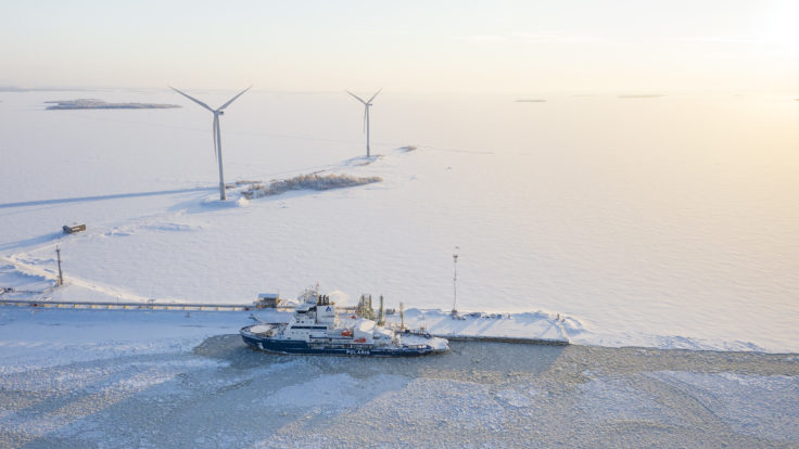 A wintry scenery of a ship and wind turbines.