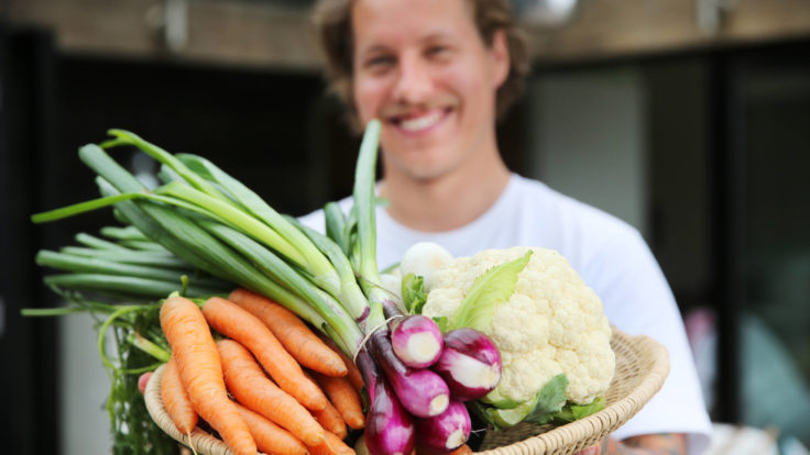 A man holding a plate full of vegetables.