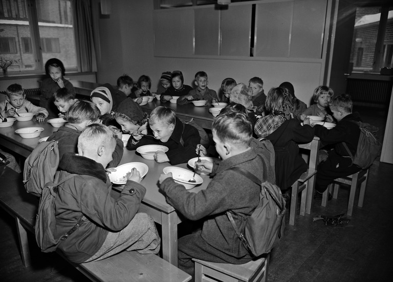 A school cafeteria filled with children eating in the 1950s.