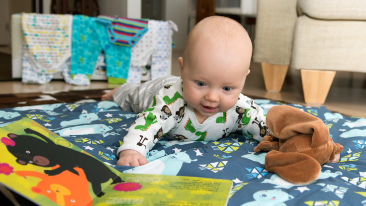 A baby on tummy time looking at a book with a maternity package and baby clothes in the background
