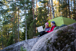 Two smiling women are camping in the forest. They are sitting on a cliff in front of their tent using a laptop.