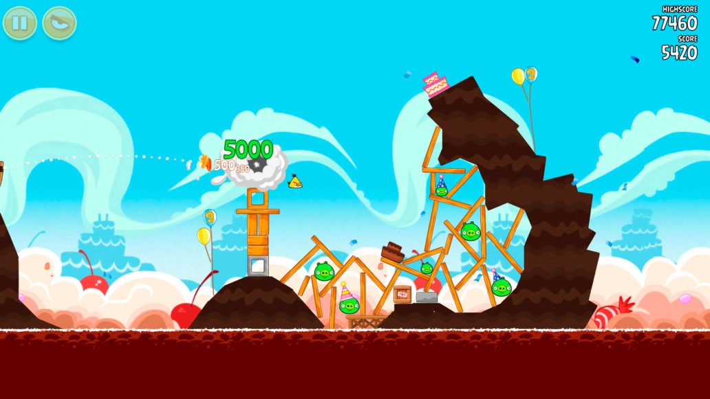 A scene from the Angry Birds game, a yellow bird flying into a wooden fort with green pigs.