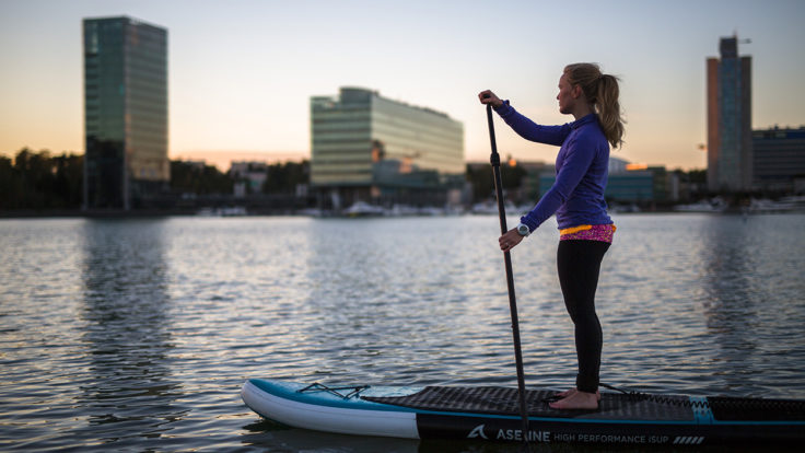 A person standing on a sup board looking into the distance, high-rise buildings in the background.