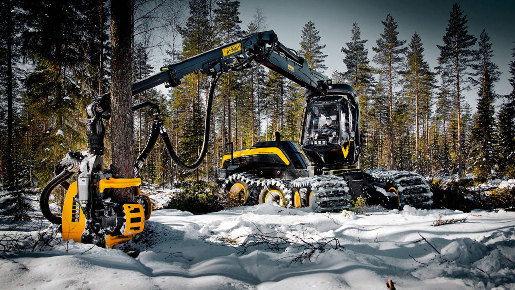 A big forestry machine at work in a snowy forest.
