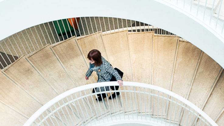 A woman walking up a spiral staircase.