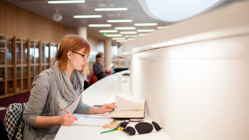 A person studying at a long white table, notebooks, pencils and a book are on the table.