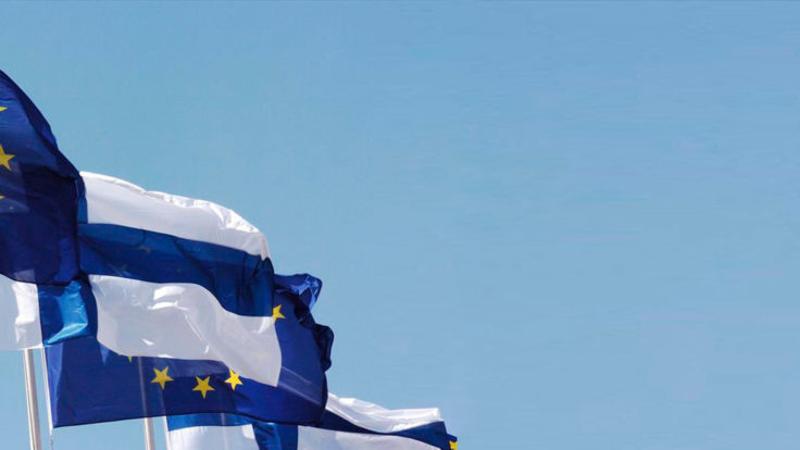 Finnish and EU flags flying against a clear blue sky.