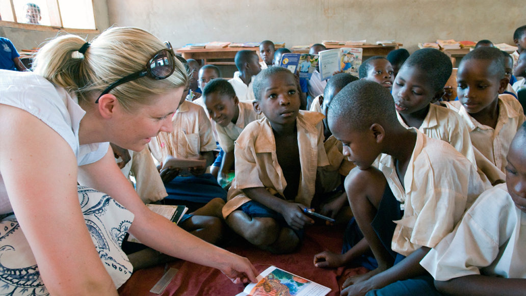 A classroom filled with young children sitting on the floor and a teacher pointing out something from a book they're reading.