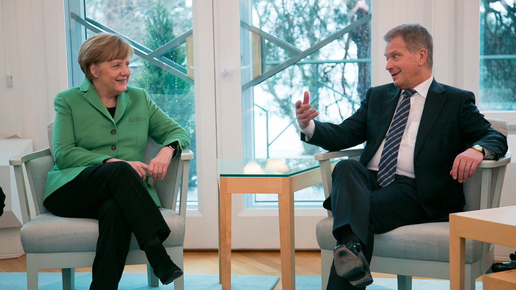 Angela Merkel and Sauli Niinistö sitting in armchairs in front of big windows and discussing.