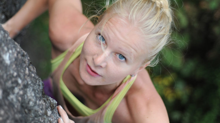 A determined-looking woman facing up while rock climbing.