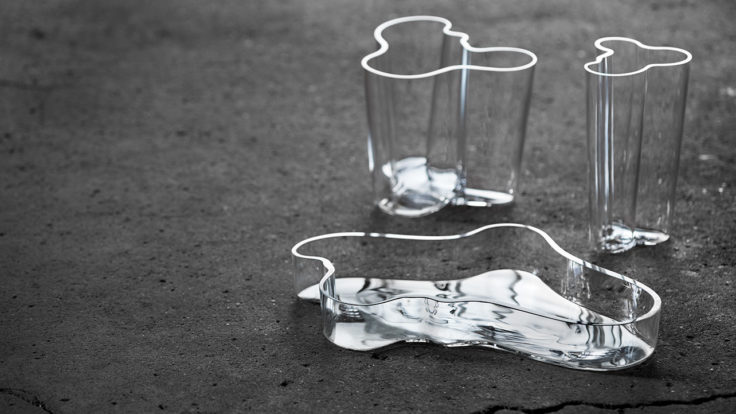 Three different-sized Aalto-vases made of clear glass sitting on dark grey concrete.