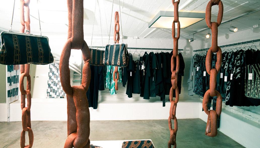 A clothing store with clothes hanging in a rack and chains made of cloth hanging from the ceiling.
