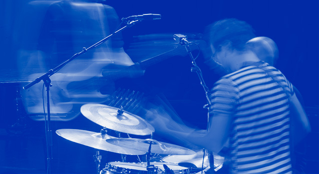 A blurred photo of a drummer drumming their kit and a guitarist playing in the background.