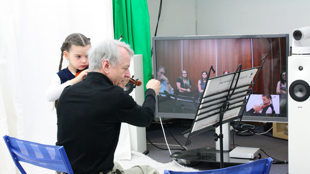 An elderly man teaching a young girl how to play the violin, online students watching them are visible on a big screen.