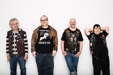 Four punk rocker men dressed in jeans and vests leaning on a white wall.