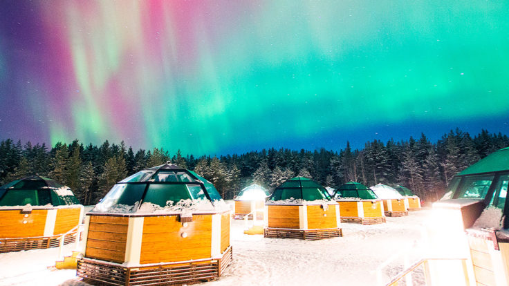 Small round huts with glass ceilings in a snowy landscape with northern lights in the sky..